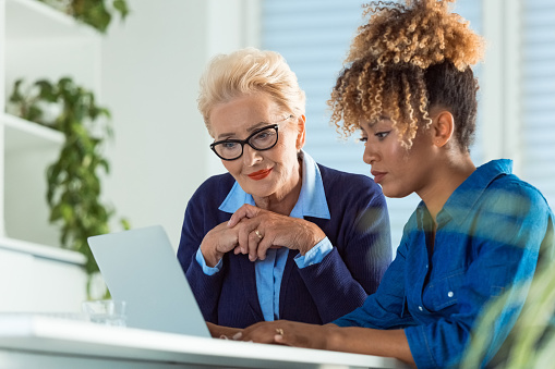 Female Business Professionals Using Laptop At Desk Stock Photo - Download Image Now