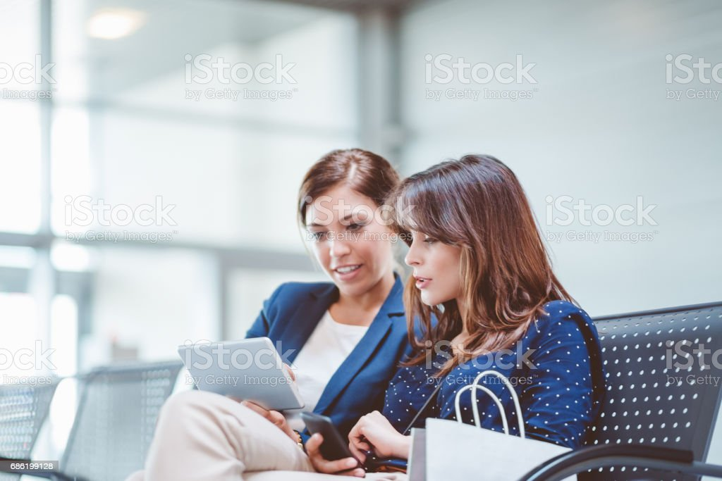 Female business travelers waiting at airport lounge stock photo