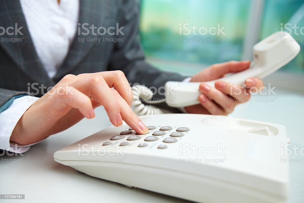 Female businesswoman dialing on a land line phone stock photo