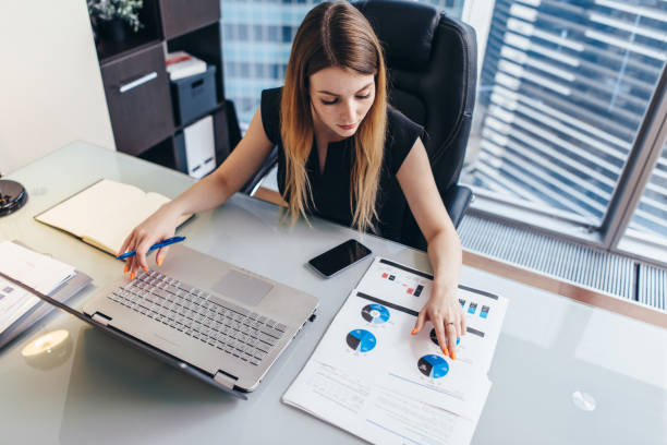 female businesswoman readind financial report analyzing statistics pointing at pie chart working at her desk - examinar imagens e fotografias de stock