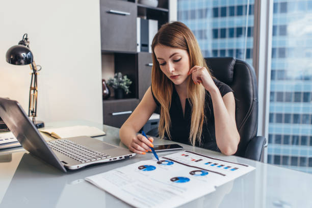 Female businesswoman readind financial report analyzing statistics pointing at pie chart working at her desk stock photo