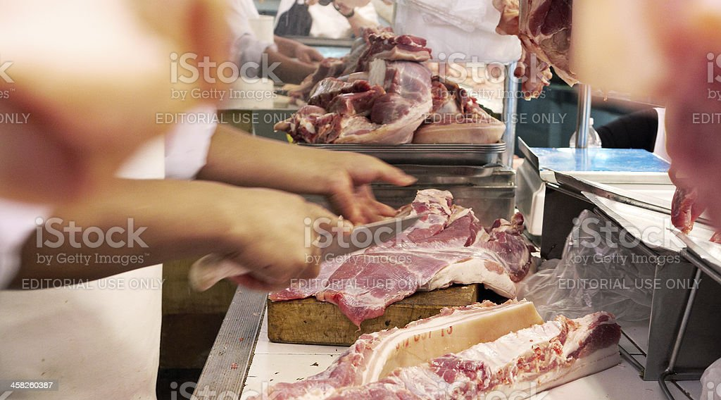 Female butcher cutting meat in Lima street market royalty-free stock photo
