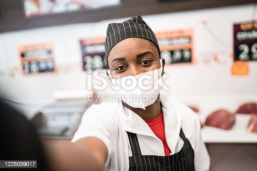Female butcher taking a selfie at butcher's shop - with face mask