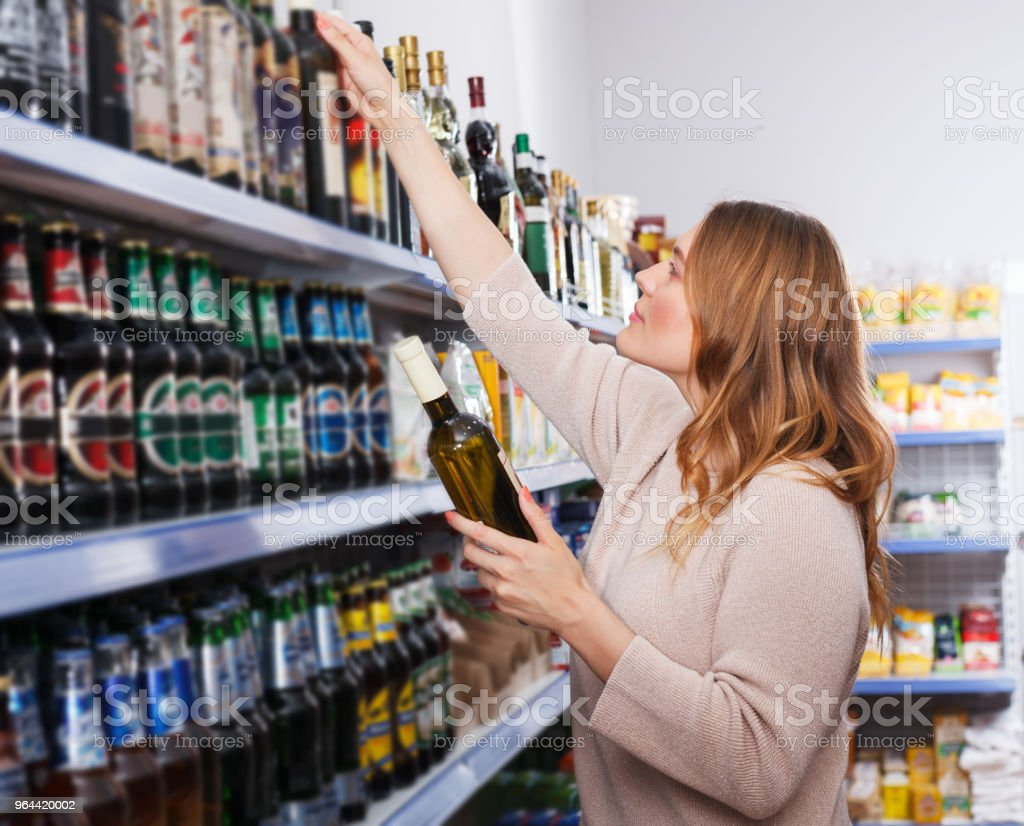 Female buying bottle of wine - Royalty-free Adult Stock Photo