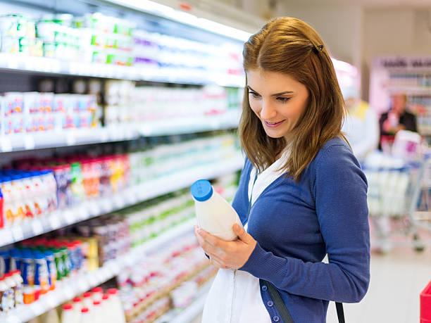 Female buying milk in supermarket stock photo