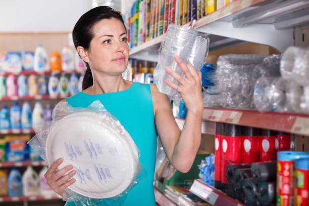 weiblich, einweggeschirr im supermarkt kaufen - teller kaufen stock-fotos und bilder