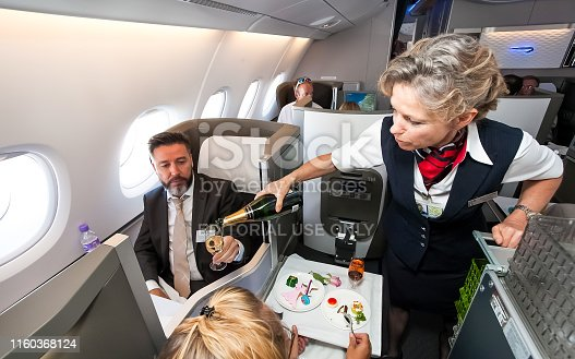 istock Female cabin crew pouring a glass of champaign in business class of an Airbus A380 1160368124
