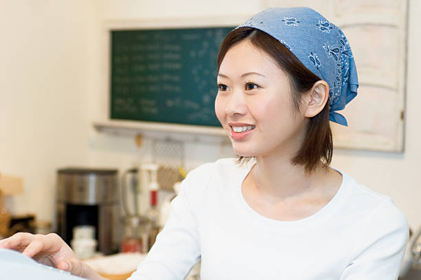 Female cafe staff typing cash register stock photo