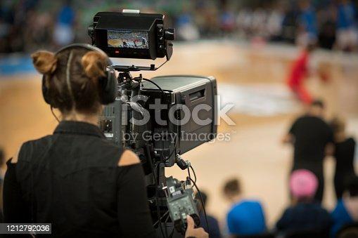 Female camerawoman shooting basketball game at Arena Stozice, Ljubljana, Slovenia.