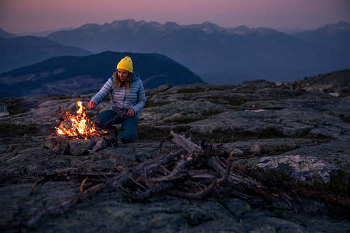 Woman in 30's making fire while camping outdoors, in an alpine wilderness near Whistler, BC, Canada.