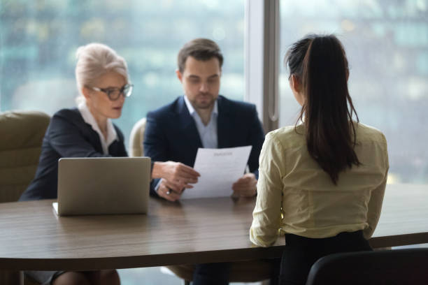 Female candidate interview with HR managers in office Back view of female candidate apply for position, interview in modern office, recruiters consider applicant candidature, reading resume, HR managers look through employee cv. Hiring concept job interview stock pictures, royalty-free photos & images
