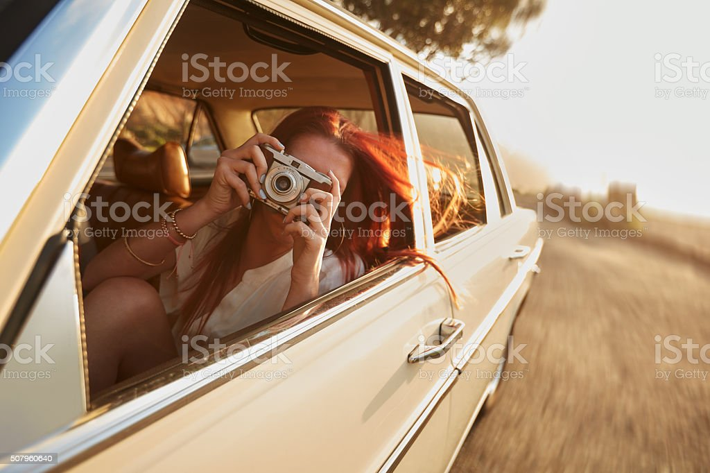 Female capturing a perfect road trip moment. stock photo