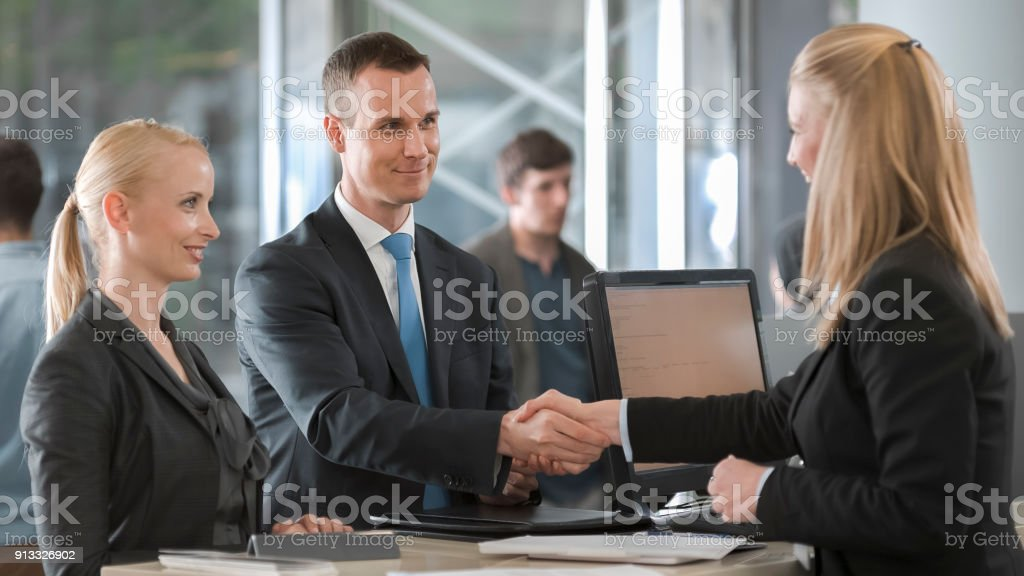 Female car rental agent shaking hands with young couple and handing them key to rental car stock photo