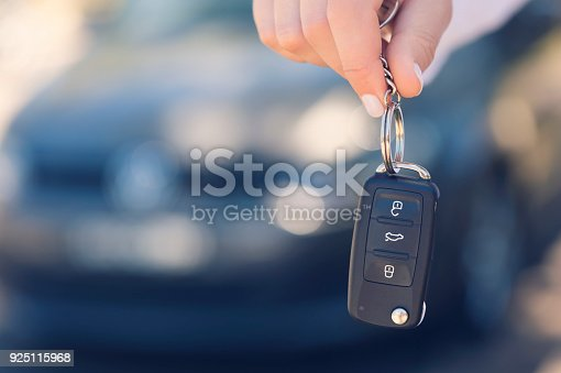 istock Female car salesperson handing  over the new car keys. 925115968