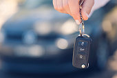 Female car salesperson handing  over the new car keys. There is a new car behind her out of focus. Close up with Copy space