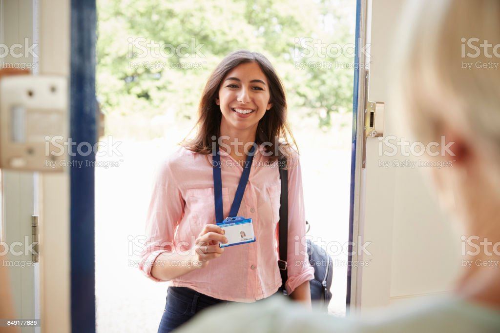Female care worker on home visit showing her ID, close up stock photo