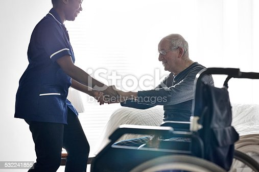 istock Female caregiver helping senior man get up from bed 532241855