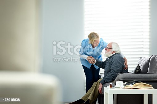 istock Female caregiver helping senior man get up from couch 478915838