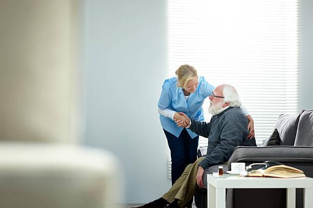 femmina caregiver aiutando uomo anziano alzarsi dal divano - prendersi cura del corpo foto e immagini stock