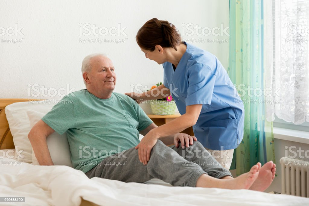 Female caregiver helping senior man stock photo