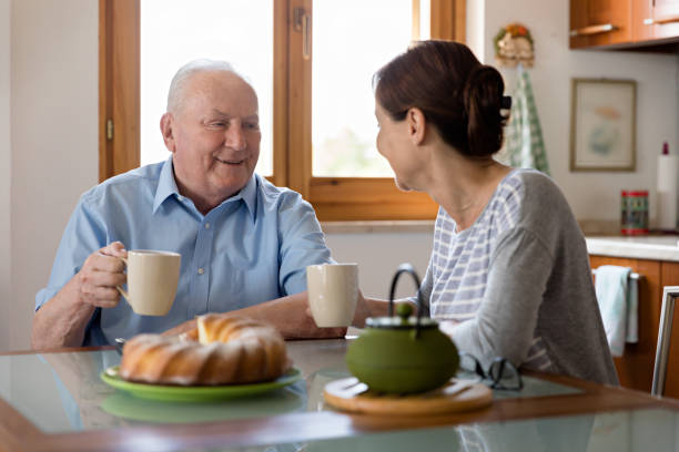 Female caregiver helping senior man stock photo