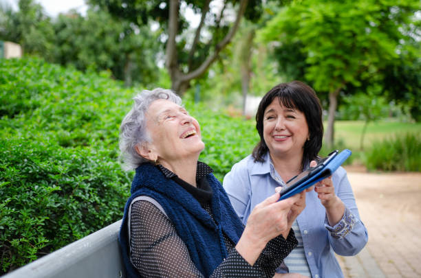 Female caregiver successfully teaches a senior woman to use a tablet sitting on a park bench stock photo