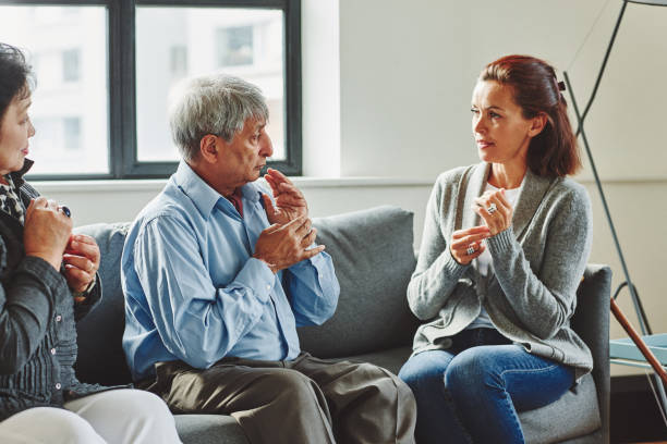 Female caregiver visiting senior couple at retirement home stock photo