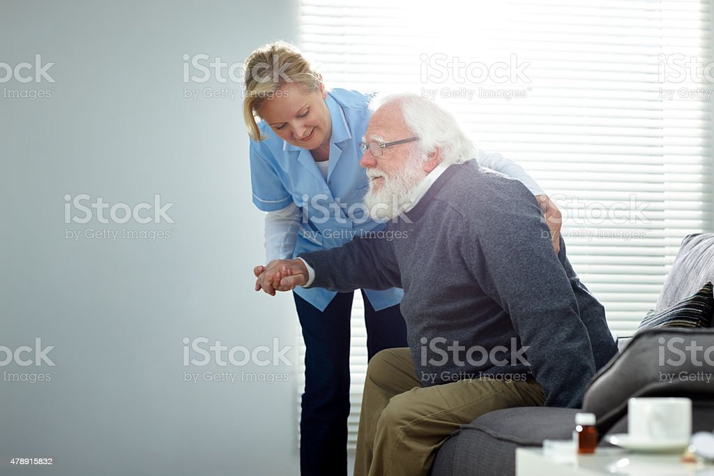 Female carer helping senior man stock photo