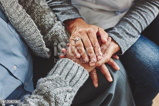 istock Female carer holding hands of senior man 912082062