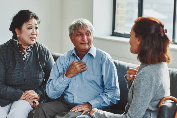 Female carer treating senior couple Female carer treating senior couple retirement home signing stock pictures, royalty-free photos & images