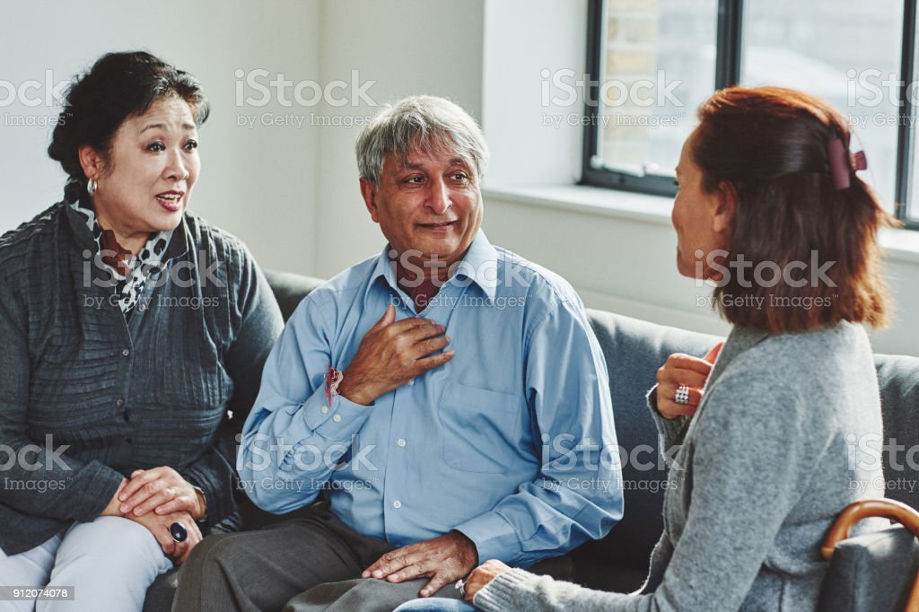 Female carer treating senior couple stock photo