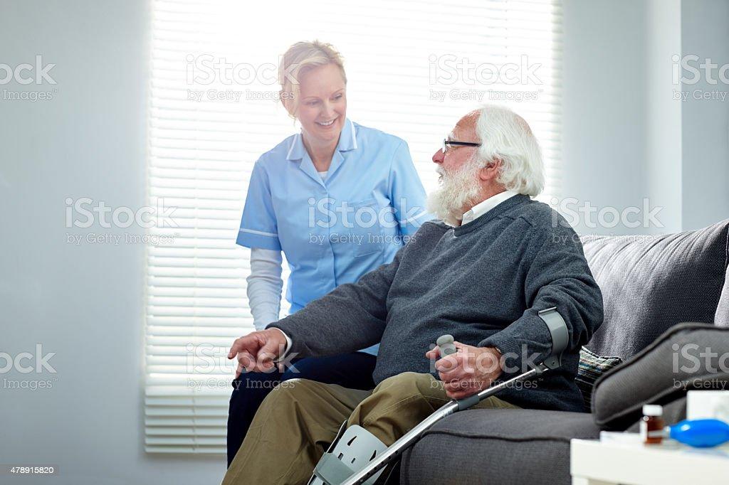 Weibliche Pflegekraft reisen mit ältere Behinderte Mann sitzt auf sofa – Foto
