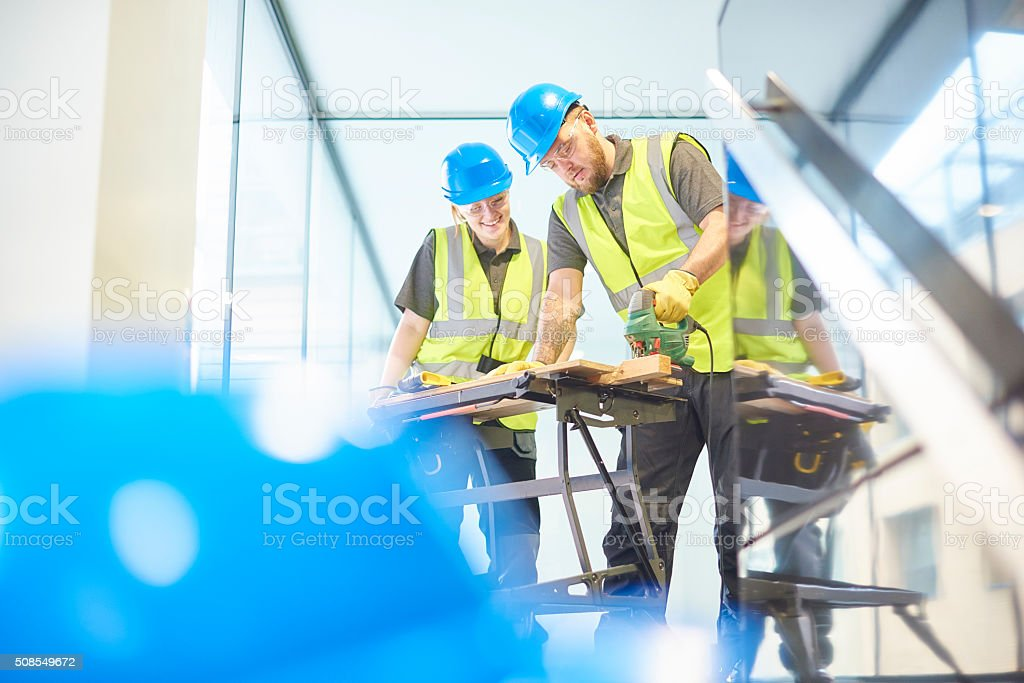 female carpenter apprentice with her colleague stock photo