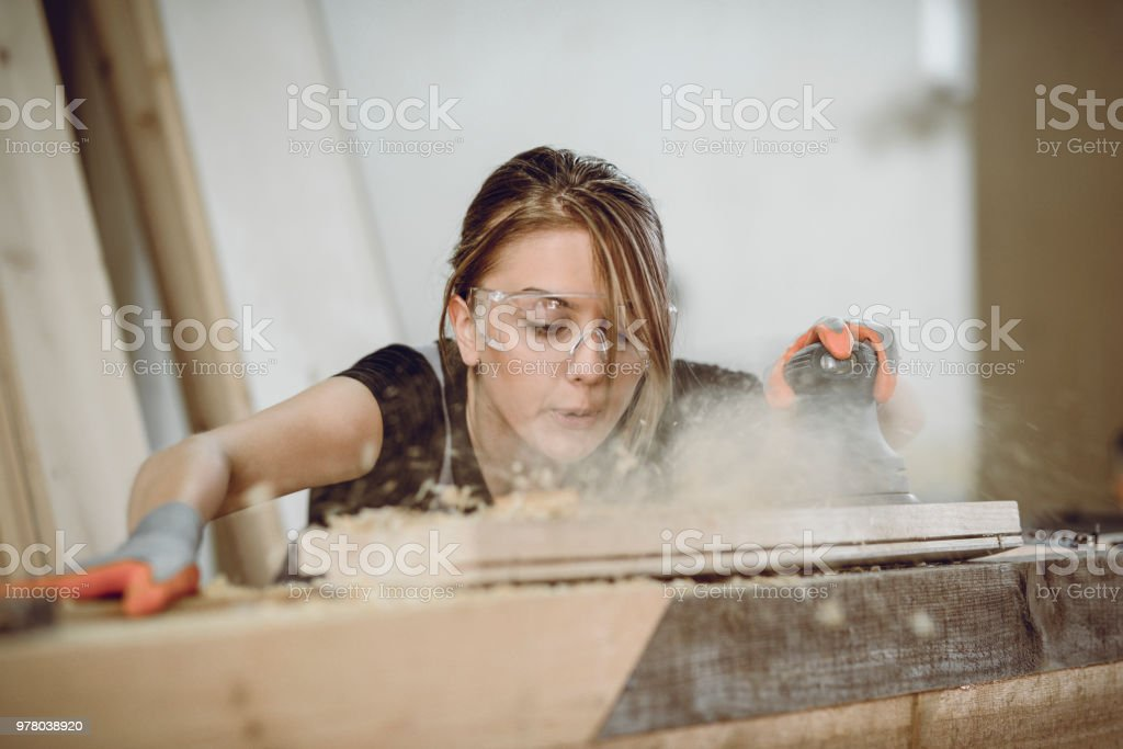 Female Carpenter Blowing Dust While Sanding Plank stock photo