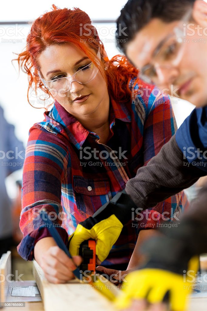 Female carpenter building something in workshop with coworker stock photo