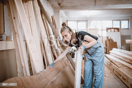 istock Female Carpenter Choosing Quality Wooden Planks For Further Work 985143522