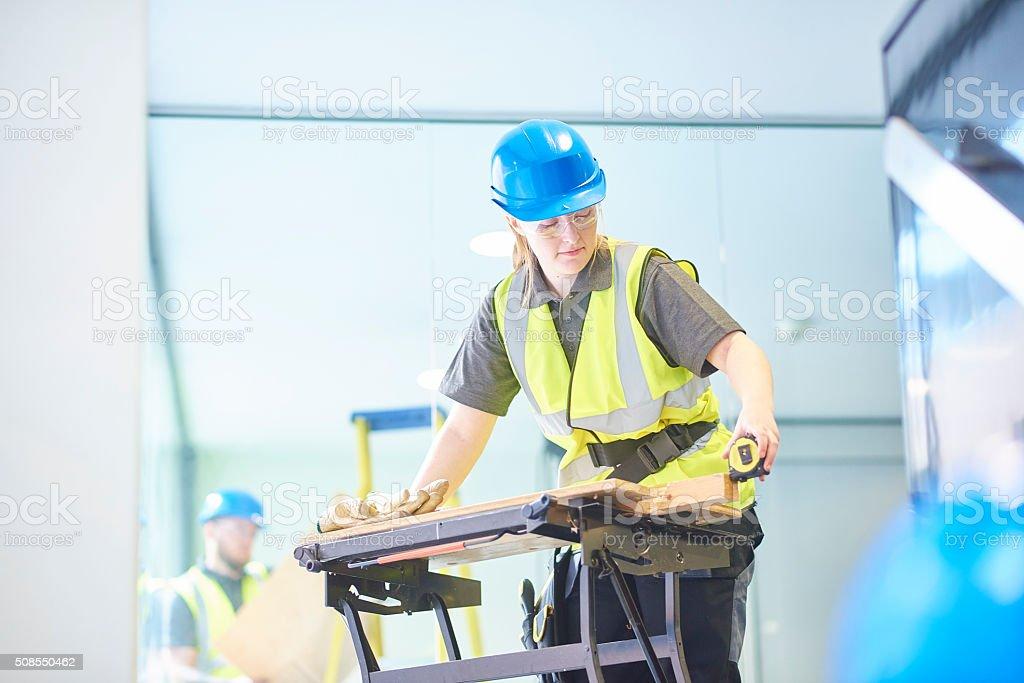 female carpenter is measuring up stock photo
