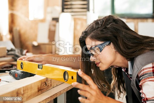 Female Carpenter looking for a curvature of a plank