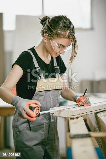 Female Carpenter Measuring Plank Length For Work