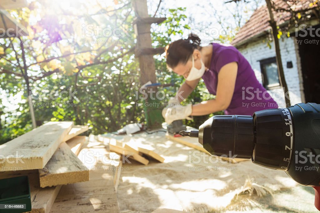 Female carpenter sanding planks stock photo