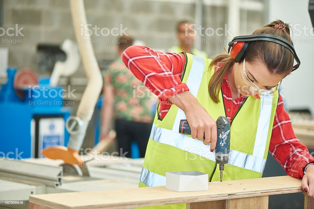 female carpenter screwing her work together stock photo