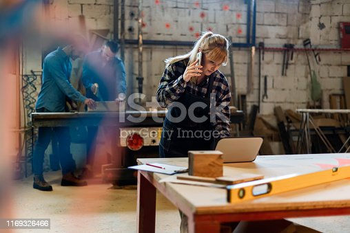 Mature Carpenter Discussing Order Details With Her Customer on Smartphone and Taking Necessary Notes, Interior of Spacious Workshop on Background. Female in Workwear Talking to Client by Smartphone While Taking Online Orders with Copy Space