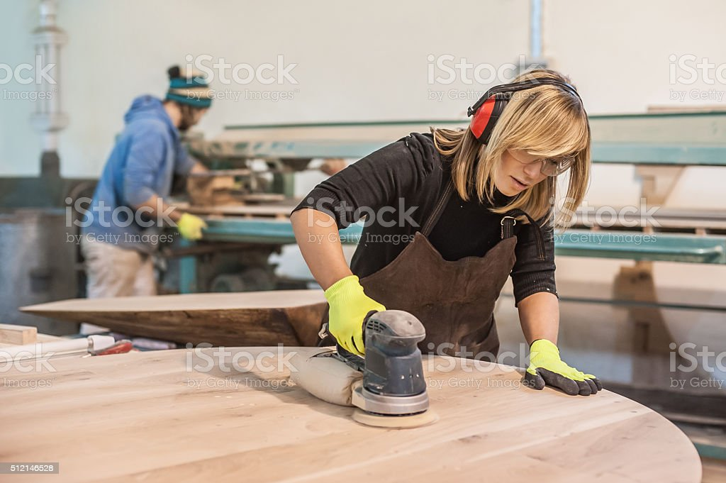 Female carpenter Using Electric Sander stock photo