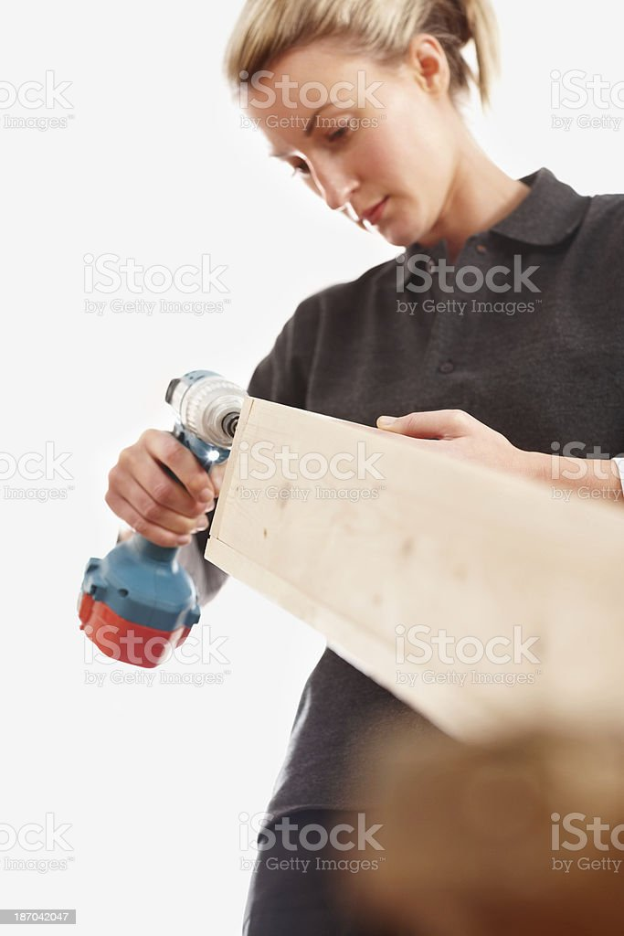 Female carpenter working with electric screwdriver royalty-free stock photo