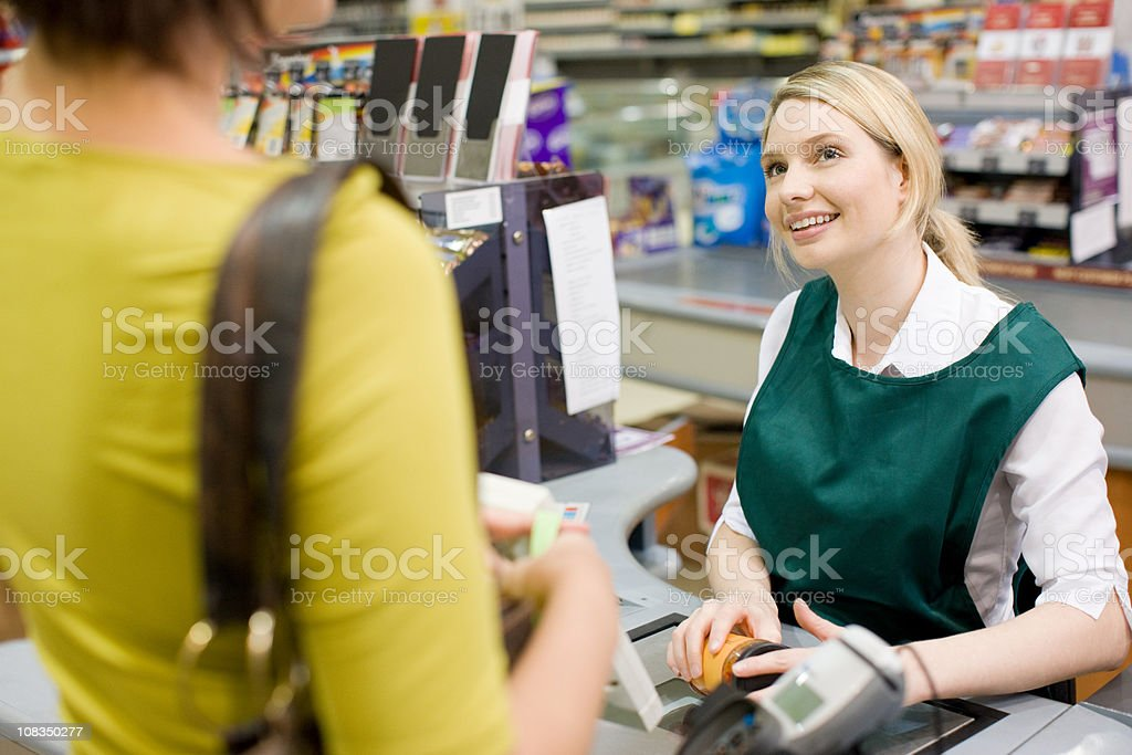 Female cashier and customer at supermarket checkout stock photo
