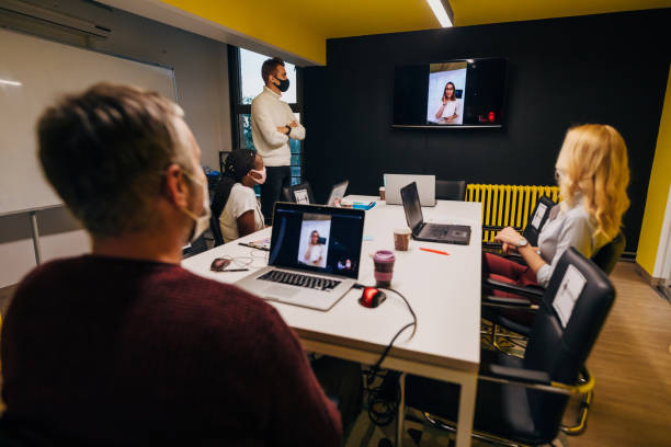 Female CEO leading a video conference while her team listening her presentation at the board room stock photo