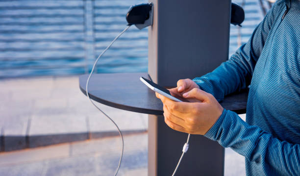 Female charging phone on a public charger Female using phone and charging on a public charger phone charging stock pictures, royalty-free photos & images