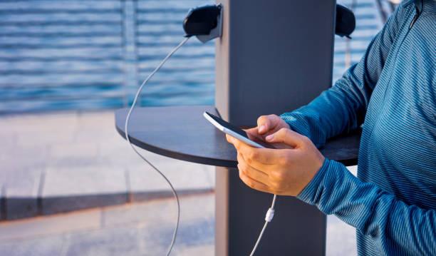 weiblich, telefon auf einem öffentlichen ladegerät aufladen - aufladen stock-fotos und bilder