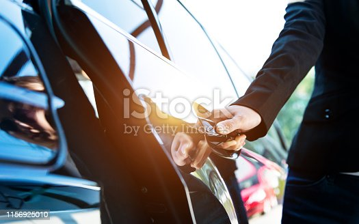 Female chauffeur opening a luxury car door.