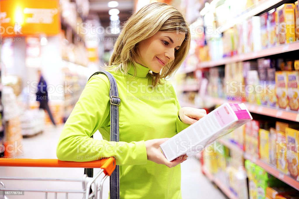 Female checking food labeling in supermarket. stock photo